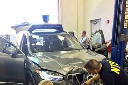 FILE- In this March 20, 2018, file photo provided by the National Transportation Safety Board, investigators examine a driverless Uber SUV that fatally struck a woman in Tempe, Ariz. Uber announced Wednesday, May 23, that it is pulling its self-driving cars out of Arizona, a reversal triggered by the recent death of woman who was run over by one of the ride-hailing service's robotic vehicles while crossing a darkened street in a Phoenix suburb. (National Transportation Safety Board via AP, File)