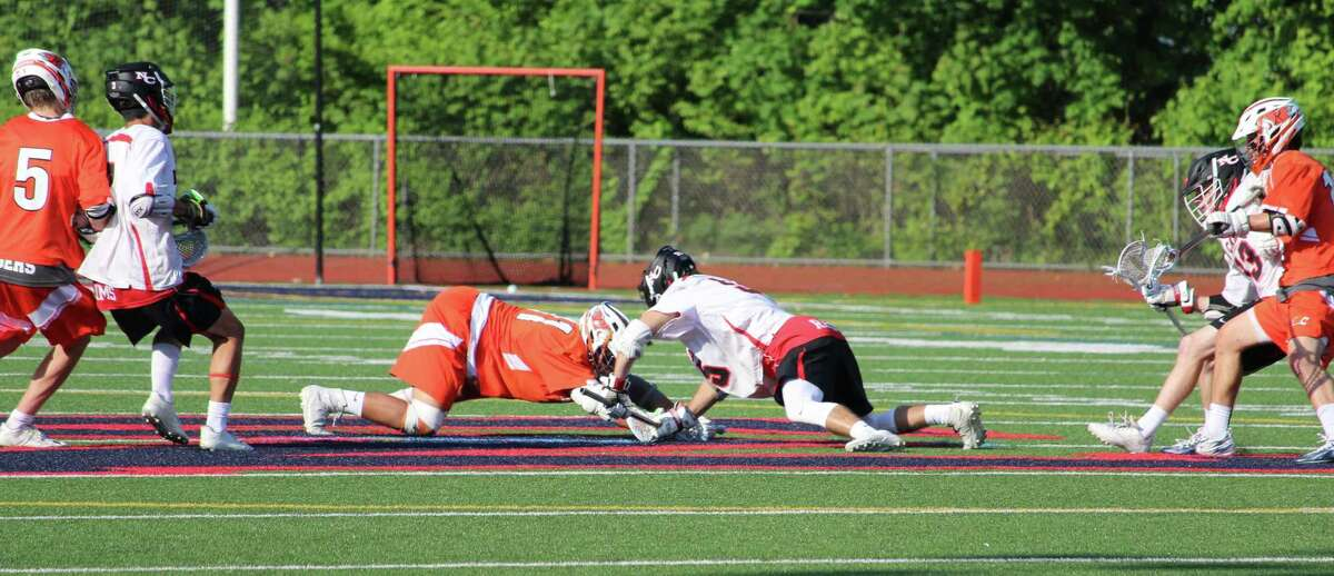 New Canaan's Nick Crovatto, right, and Ridgefield's Chris D'Entrone battle for a faceoff during the FCIAC boys lacrosse semifinals Wednesday in Norwalk.