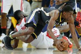Golden State Warriors' Kevon Looney scrambles for a loose ball in the first quarter during game 4 of the Western Conference Finals between the Golden State Warriors and the Houston Rockets at Oracle Arena on Tuesday, May 22, 2018 in Oakland, Calif.
