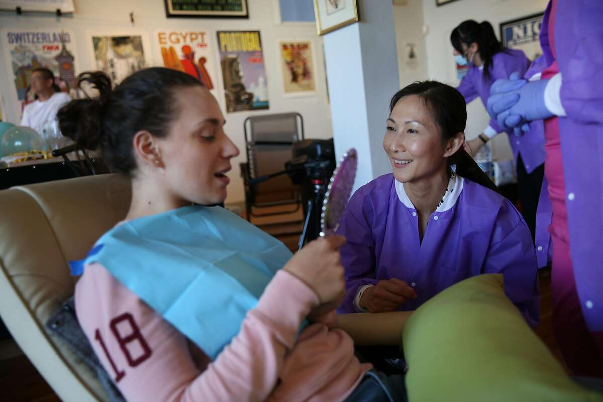From left: Sara Peric checks her teeth after a whitening session with Gloria Vo at Dazzle Bar, Friday, May 11, 2018, in San Francisco, Calif. Dazzle Bar, a pop-up breath freshening and teeth whitening service, was held at the Real Old Paper Gallery in the North Beach neighborhood.