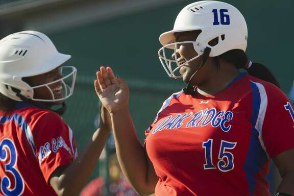 Oak Ridge's Taylor Brandon, right, shares a laugh with Rhian Journey after Journey scored on an error in the first inning of Game 2 during a Region II-6A semifinal series at Montgomery High School, Friday, May 18, 2018, in Montgomery.