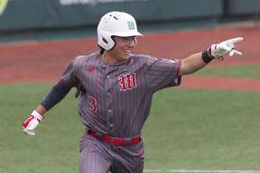 Casey Sunseri #3 of The Woodlands points toward Will Swope as he scores on Swope's triple in the first inning of Game 1 during a Region II-6A semifinal series at Sam Houston State University, Wednesday, May 23, 2018, in Huntsville.