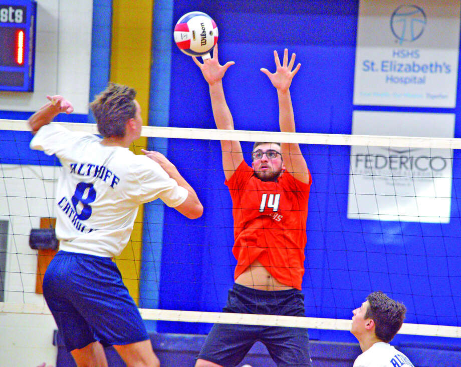Edwardsville senior Drew Berthlett, right, goes up for a block during Wednesday's match against Belleville Althoff in  the championship match of the Althoff Regional.
