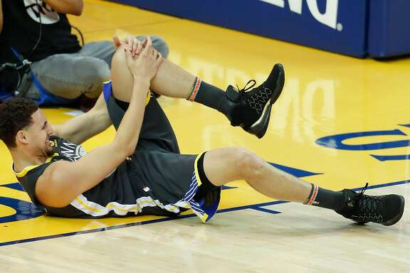 Golden State Warriors' Klay Thompson holds his knee after coming down hard in the second quarter during game 4 of the Western Conference Finals between the Golden State Warriors and the Houston Rockets at Oracle Arena on Tuesday, May 22, 2018 in Oakland, Calif.