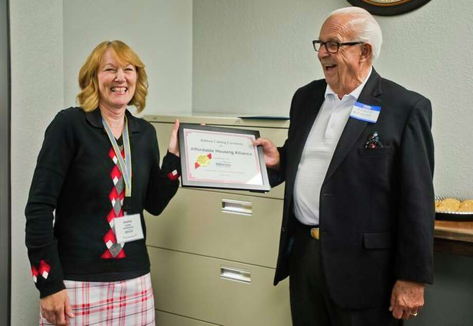 Shelly Hobbs of Isabella Bank awards a plaque to Affordable Housing Alliance Executive Director Roger Mikusek during a ribbon cutting ceremony for the organization's new location at 3400 Isabella St. on Monday afternoon. (Katy Kildee/kkildee@mdn.net)