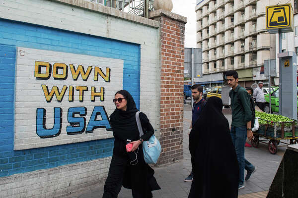 Pedestrians pass a wall mural proclaiming 'Down With The USA' on a street in Tehran, Iran, on May 9, 2018.