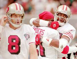 San Francisco 49ers wide receiver Jerry Rice, right, celebrates a first half touchdown with cornerback Deion Sanders, center, as quarterback Steve Young (8) looks on at the Georgia Dome in Atlanta Sunday, Oct. 16, 1994. The 49ers downed the Falcons 42-3 and Young went 15-for-16 and 143 yards with 4 TDs. (AP Photo/John Bazemore)