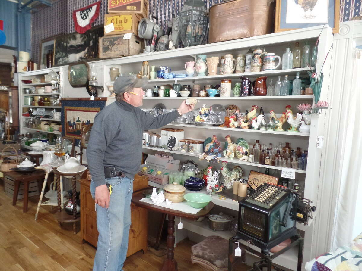Owner Doug Deming arranges a small portion of the antiques and collectables available at Cornerstone Venture. The store is located at 4 N. Center in Sebewaing.