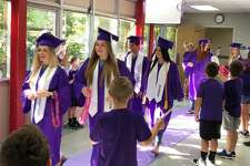 The 2018 Port Neches-Groves seniors walk through the halls of Woodcrest Elementary Thursday, May 24, 2018.