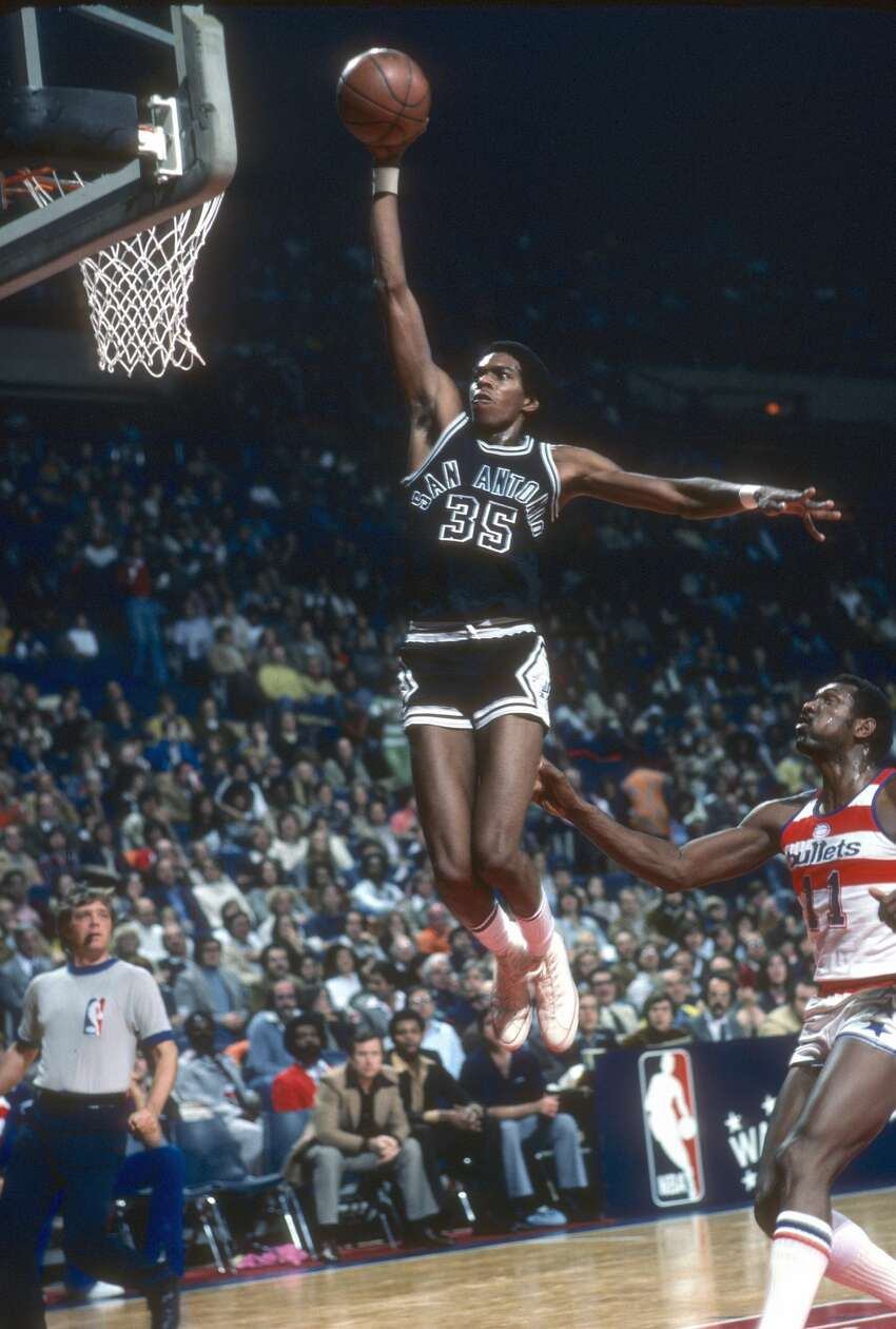 LANDOVER, MD - CIRCA 1978: Larry Kenon #35 of the San Antonio Spurs goes up for a slam dunk over Elvin Hayes #11 of the Washington Bullets during an NBA basketball game circa 1978 at the Capital Centre in Landover, Maryland. Kenon played for the Spurs from 1975-80. (Photo by Focus on Sport/Getty Images)