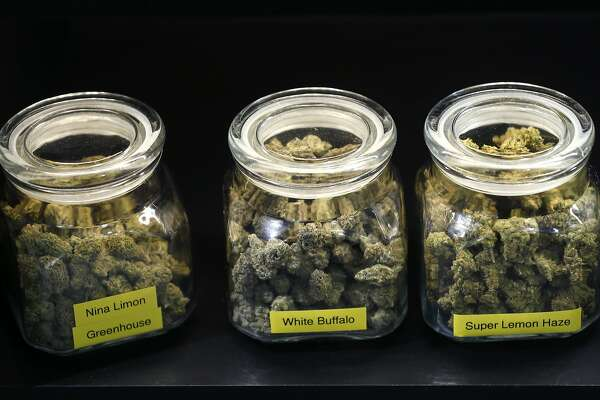 Jars of medicinal marijuana are stored under the counter at The Apothecarium dispensary in San Francisco, Calif. on Friday, Dec. 29, 2017. The rules may vary for medicinal cannabis users that hold a locally-issued medical card instead of one officially issued by the state once public sales of marijuana becomes legal Jan. 1.