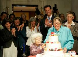Del Martin, left, and Phyllis Lyon, right, cut their wedding cake after being married by San Francisco Mayor Gavin Newsom, standing behind them, at City Hall in San Francisco, Monday, June 16, 2008. On Monday afternoon the same-sex couple was the first to be legally married by the mayor. (AP Photo/Eric Risberg)