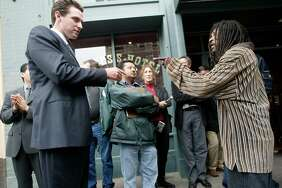 Gavin Newsom and homeless man Frank Johnson discuss the mayor's Care Not Cash program outside the Empress Hotel on Eddy Street in October 2004.