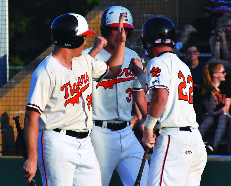Edwardsville's Reid Hendrickson, left, and Jack Cooper, center, are congratulated by Colin Elvers after they scored in the first inning against Alton on Friday.
