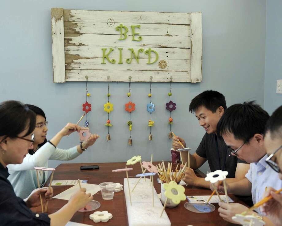 Summer interns at Boehringer Ingelheim, paint flowers that will be used in the making of Ben's Bells, Wednesday, July 29, 2015. Ben's Bells has outgrown its Newtown space and is moving to a new building in Bethel. They include from left, Yiyi Chu, Hee-Koung Joeng, Xiaoqi Lu, Guan Yu and Yaohua Zhang. Photo: Carol Kaliff / Hearst Connecticut Media / The News-Times