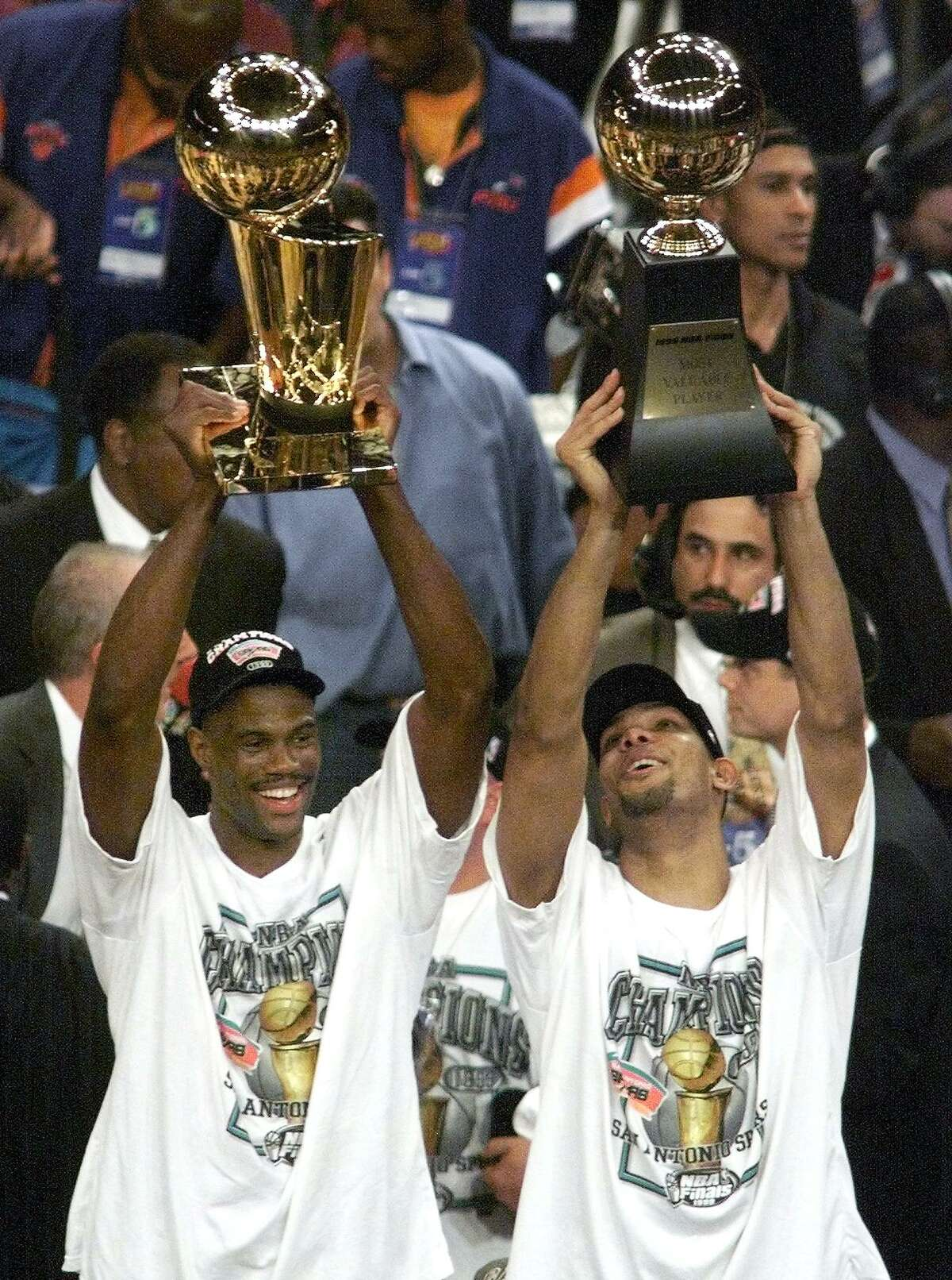 NEW YORK, UNITED STATES: Tim Duncan (R) of the San Antonio Spurs holds the MVP trophy as David Robinson holds the championship trophy 25 June, 1999, after the Suprs won game five of the NBA Finals against the New York Knicks at Madison Square Garden in New York, NY. The Spurs won the game 78-77 to win the series four games to one. (ELECTRONIC IMAGE) AFP PHOTO/Timothy A. CLARY (Photo credit should read TIMOTHY A. CLARY/AFP/Getty Images)