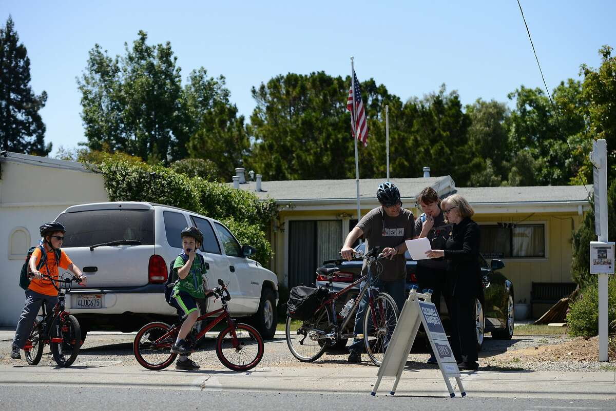 Realtor Cheryl Rivera Smith, far right, shows renderings of a proposed home to the Nathan and Jennifer Laredo, from Mountain View, trailed by sons Miles, age 7, and Noah, age 9, who stopped by an Open House at 372 Farley Street in Mountain View on Saturday May 19, 2018.