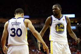 HOUSTON, TX - MAY 14:  Kevin Durant #35 and Stephen Curry #30 of the Golden State Warriors react after a play in the third quarter against the Houston Rockets in Game One of the Western Conference Finals of the 2018 NBA Playoffs at Toyota Center on May 14, 2018 in Houston, Texas. NOTE TO USER: User expressly acknowledges and agrees that, by downloading and or using this photograph, User is consenting to the terms and conditions of the Getty Images License Agreement.  (Photo by Ronald Martinez/Getty Images)