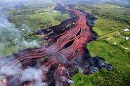 """HAWAII, USA - MAY 22: (----EDITORIAL USE ONLY  MANDATORY CREDIT - """"USGS / HANDOUT"""" - NO MARKETING NO ADVERTISING CAMPAIGNS - DISTRIBUTED AS A SERVICE TO CLIENTS----) Ash plume rises from forest following a massive volcano eruption on Kilauea volcano in Hawaii, United States on May 22, 2018. Lava is spewing more than 60 metres into the air and spread around 36,000 square metres. (Photo by USGS / Handout/Anadolu Agency/Getty Images)"""