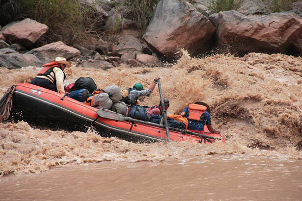 Passengers hold on tightly on the world-class white water of the Colorado River as it runs through the Grand Canyon. Tight life jackets and good handholds are essential.