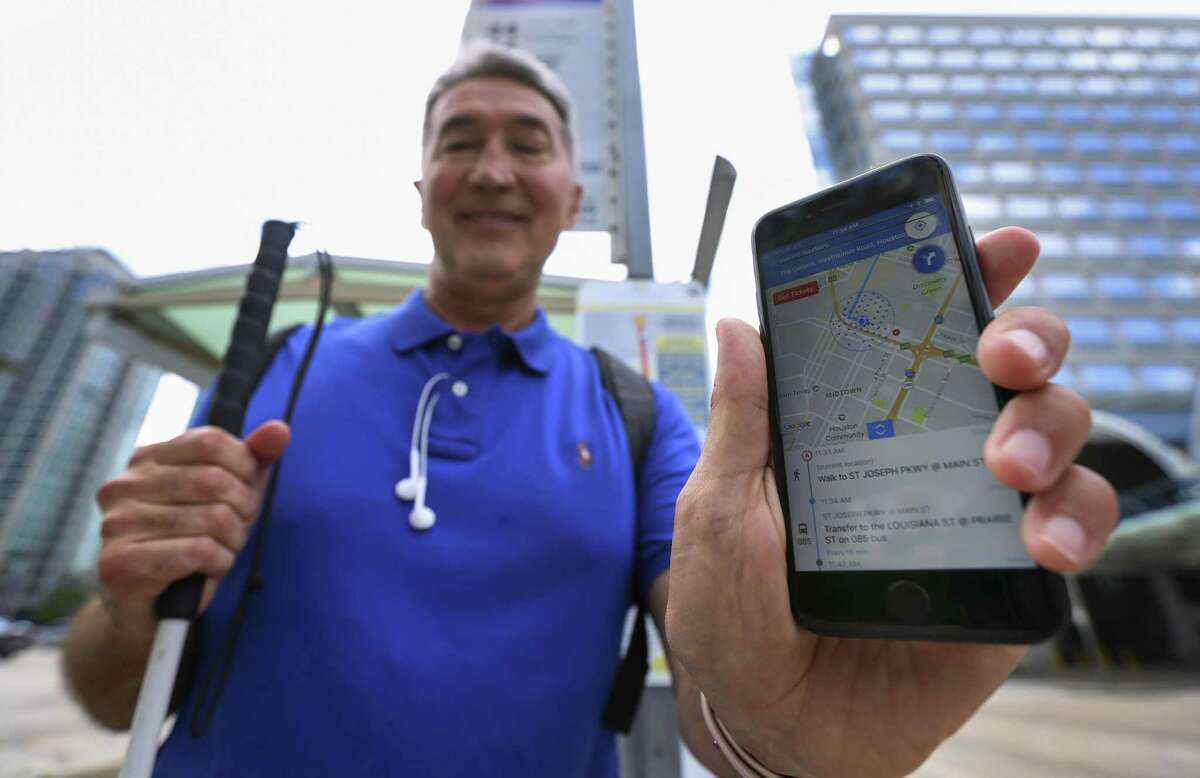 Michael McCulloch, 63, a member of the test group that helps Metropolitan Transit Authority experiment with Bluetooth beacons, poses with an app-in-progress that he is assisting to develop for visually-impaired passengers at a bus stop on May 24.