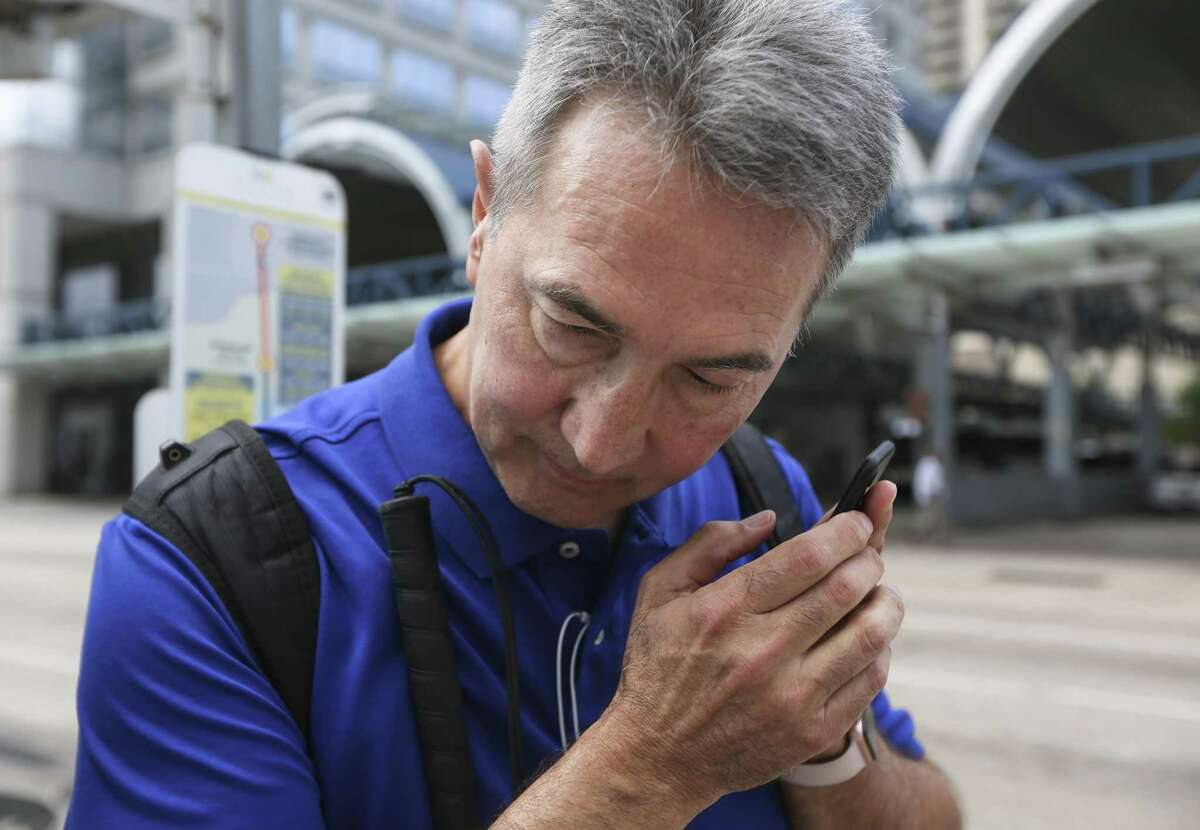 Michael McCulloch, 63, a member of the test group that helps Metropolitan Transit Authority experiment with Bluetooth beacons, listens to the audio commands from an app-in-progress that he is assisting to develop for visually-impaired passengers at a bus stop on May 24.