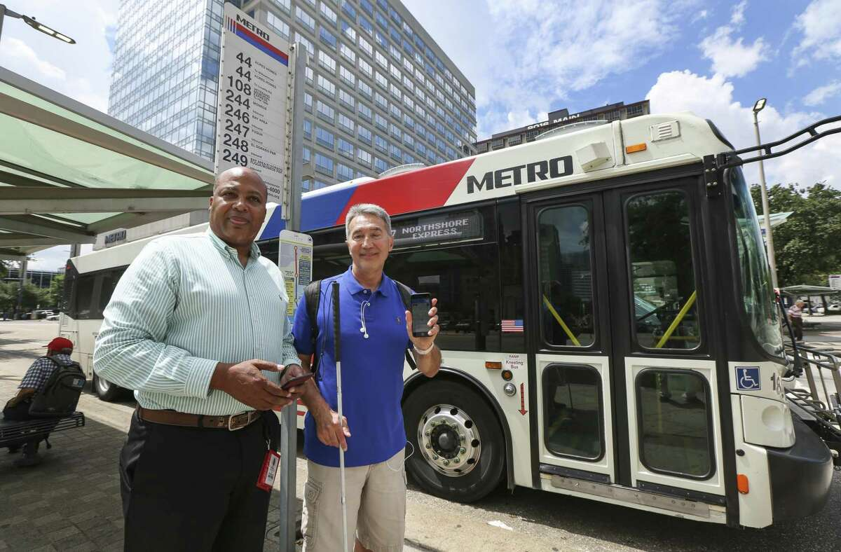 Metropolitan Transit Authority Chief Technology Officer Randy Frazier, left, and Michael McCulloch, 63, a member of the test group helping Metro experiment with Bluetooth beacons, stand at a downtown Houston bus stop on May 24.