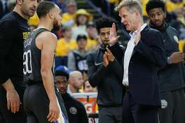 Golden State Warriors' head coach Steve Kerr talks to Stephen Curry during a first quarter timeout during game 4 of the Western Conference Finals between the Golden State Warriors and the Houston Rockets at Oracle Arena on Tuesday, May 22, 2018 in Oakland, Calif.