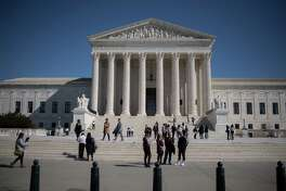 Visitors stand outside the U.S. Supreme Court in Washington on Feb. 27, 2018.