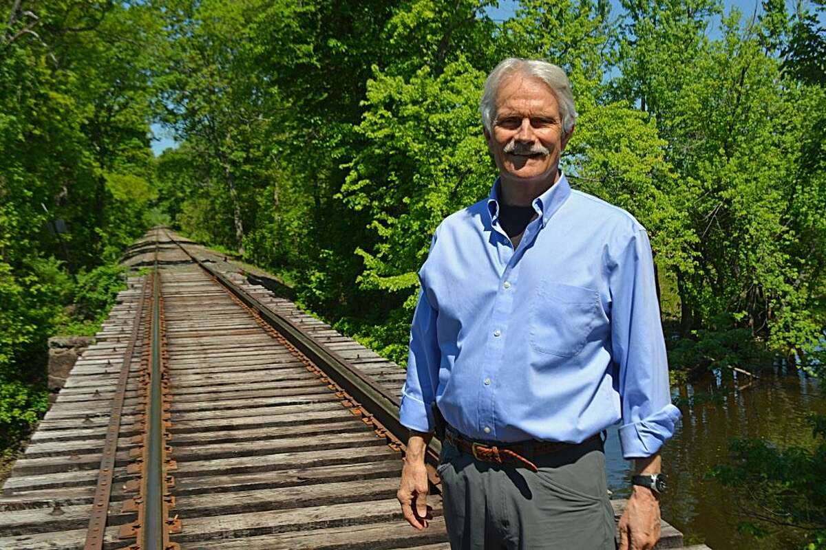 John Hall, executive director of the Jonah Center in Middletown, stands on the railroad trestle off Johnson Street near the boat launch, near where a biking/hiking trail will soon make its way around the landfill. It will include a path up to the peak of the transfer station, where there will be a sweeping view of the area.