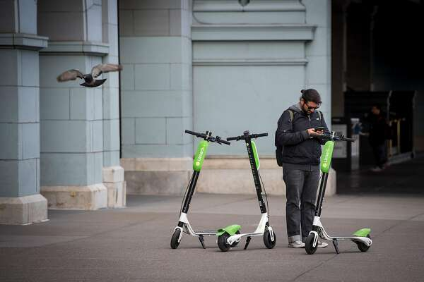 A rider checks the status of a LimeBike scooter in San Francisco, California, U.S., on Tuesday, May 15, 2018. Neutron Holdings Inc. LimeBike is one of a handful of companies that�have spent the last few months sprinkling hundreds of bikes and�electric�scooters around American�cities. They allow�people to unlock the�vehicles with smartphone apps and ride them for as little as $1, leaving them sitting on the sidewalk when they've reached their destination. Photographer: David Paul Morris/Bloomberg