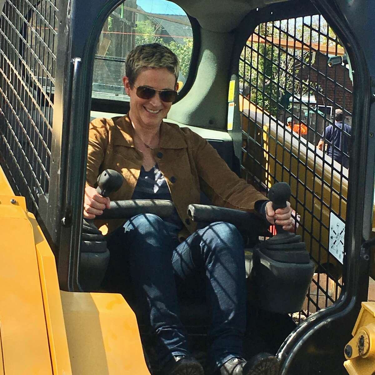 Red Oak Realty agent Maxi Lilley drives a Bobcat during the demolition of 5355 Manila in Oakland.