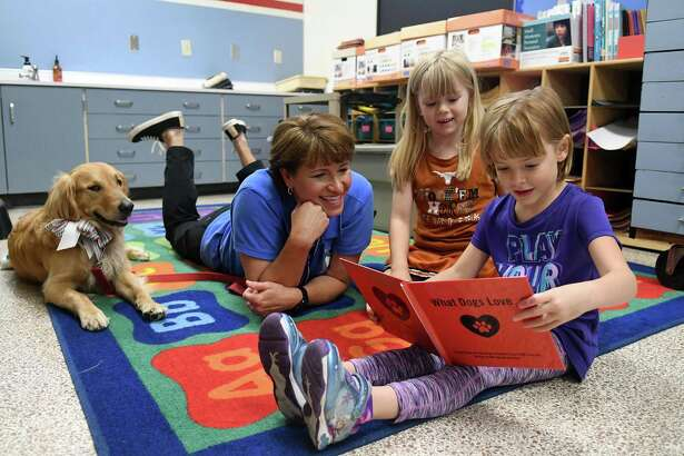 """Melinda Blankenship, left, of Spring, with her therapy dog """"Piper"""", listens as Theiss Elementary kindergartners Kamryn Milleson, 6, right, and Aubrey Whipple, 6, read to """"Piper"""" as part of the Faithful Paws PERK (Pets Enjoy Reading Kids) Program at the school on May 23, 2018. (Jerry Baker/For the Chronicle)"""