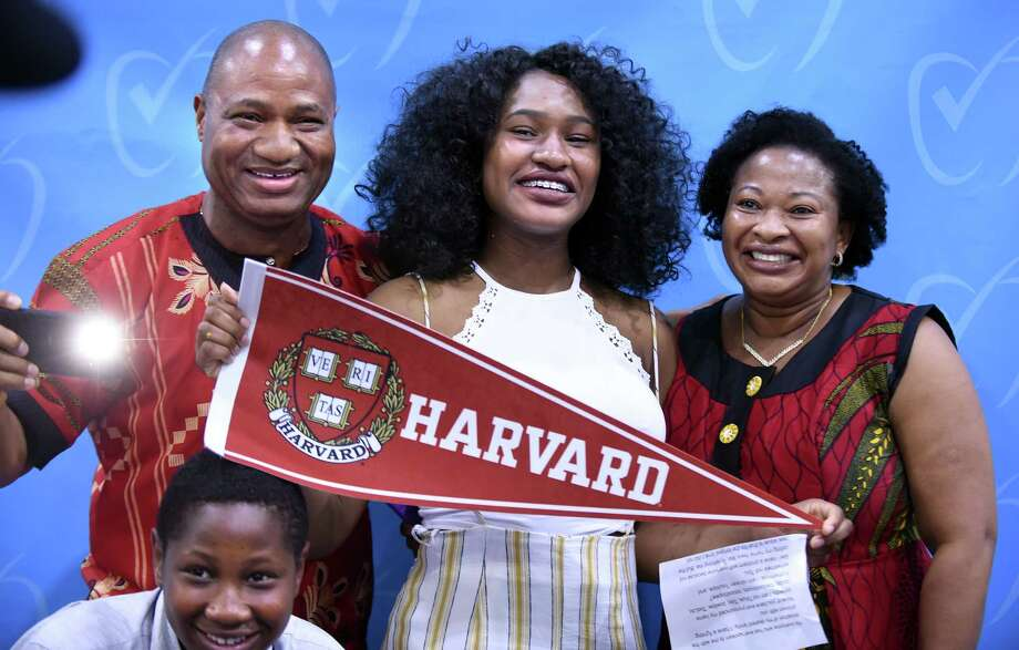 Tolulope Adeniji (center) displays the Harvard banner where she will attend college in the fall during Senior Signing Day at Achievement First Amistad High School in New Haven on May 24, 2018.  Surrounding her are her brother, Victor (bottom), 12, father, Rasaq (left), and mother, Kehinde (right), of Bridgeport. Photo: Arnold Gold, Hearst Connecticut Media / New Haven Register