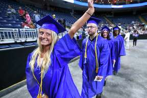 Kayleigh Roy of Wallingford waves to family as she enters Webster Bank Arena for the 26th Commencement of Gateway Community College in Bridgeport on May 24, 2018.