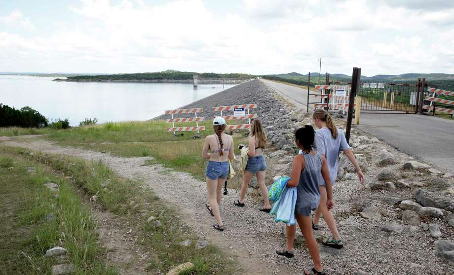 A group heads down to the water for a swim as signs show that the Army Corps of Engineers has closed the walkway atop Canyon Lake Dam on May 24, 2018. Photo: Tom Reel, San Antonio Express-News / 2017 SAN ANTONIO EXPRESS-NEWS