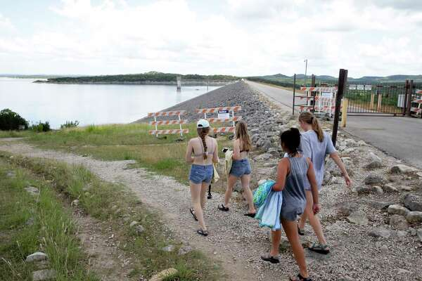 A group heads down to the water for a swim as signs show that the Army Corps of Engineers has closed the walkway atop Canyon Lake Dam on May 24, 2018.