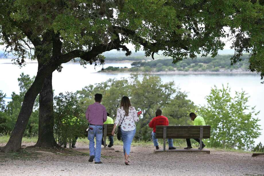 Lunch time visitors picnic on benches overlooking the water as signs show that the Army Corps of Engineers has closed the walkway atop Canyon Lake Dam on May 24, 2018. Photo: Tom Reel, San Antonio Express-News / 2017 SAN ANTONIO EXPRESS-NEWS