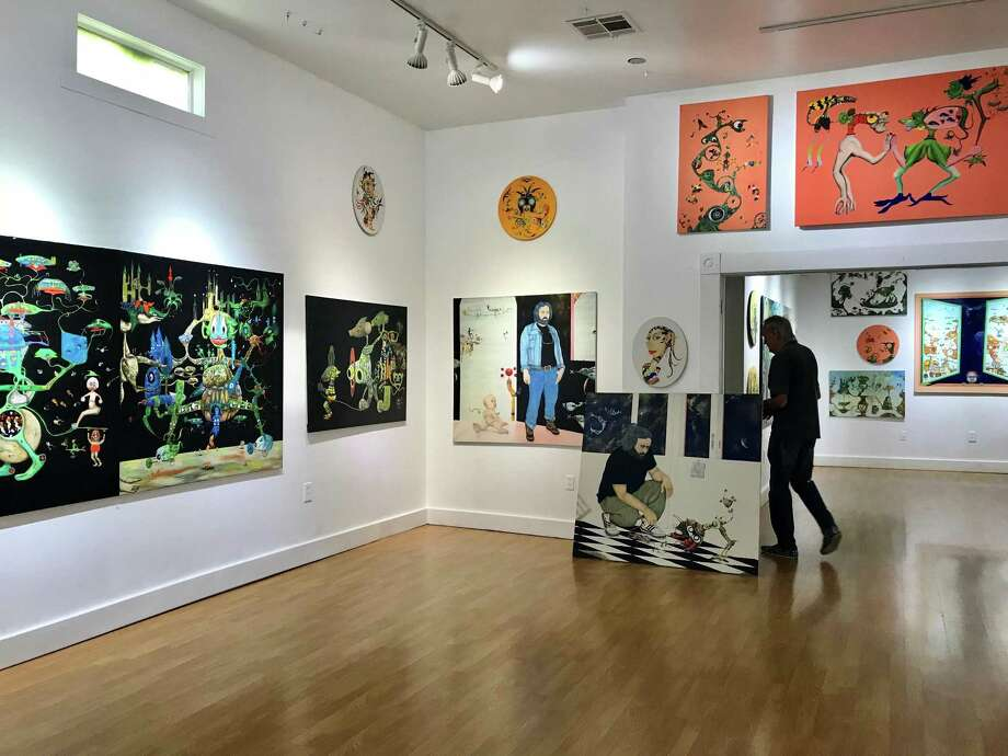 GSpot Contemporary Art Space owner Wayne Gilbert on May 17, 2018 with paintings he is featuring through May 27 by Leandra di Buelna Jr., a previously unknown visionary artist from Houston who is 82 years old. Photo: Molly Glentzer / Houston Chronicle