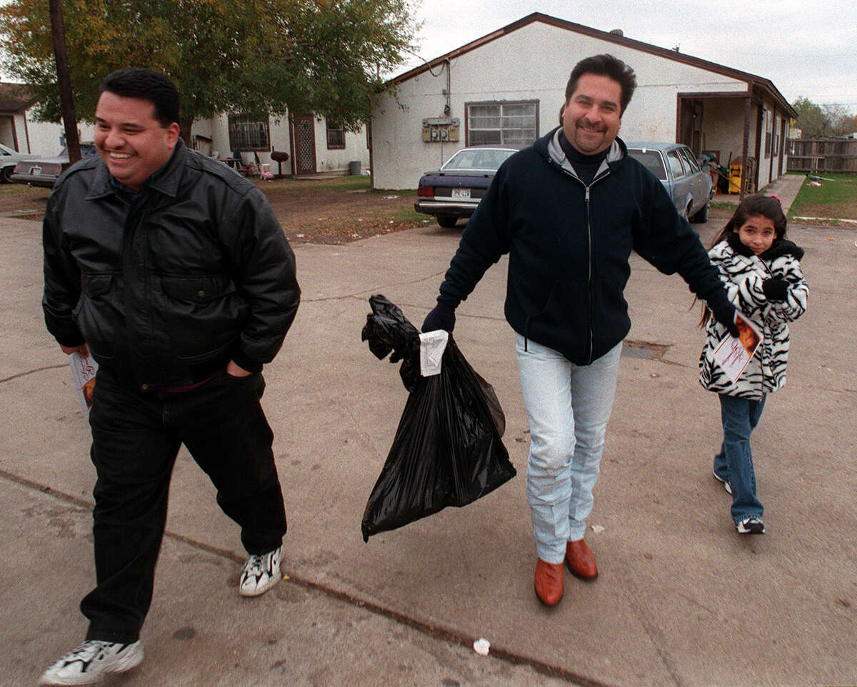 Tejano music artist Ram Herrera (Center) delivers toys and food to needy families at the Palo Alto Homes off South Zarzamora on Christmas Eve (Thursday December, 24, 1998) with the help of his manager Mark Grado (L) and his daughter Katherine Rose Herrera, 8 (rt.). The deliveries were a part of