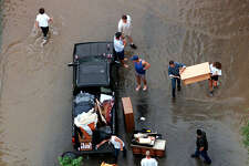 FLOODS -- Victoria residents gather whatever belongings they can salvage from their flooded homes as the Guadalupe River spills over its banks and onto streets Tuesday Oct. 20, 1998. PHOOT BY DOUG SEHRES