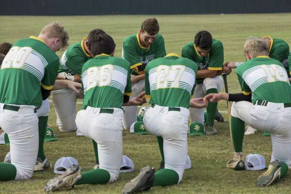 The Santa Fe High School baseball team prays before the its last game of the season Saturday, one day after a gunman killed 10 people at the school. A reader says the shooting makes it clear that legislators must act to end the horrific violence.