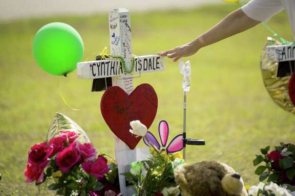 A woman gestures toward a cross honoring Santa Fe High School substitute teacher Cynthia Tisdale Tuesday, who was killed during a shooting at the school on Friday, in Santa Fe, Texas.