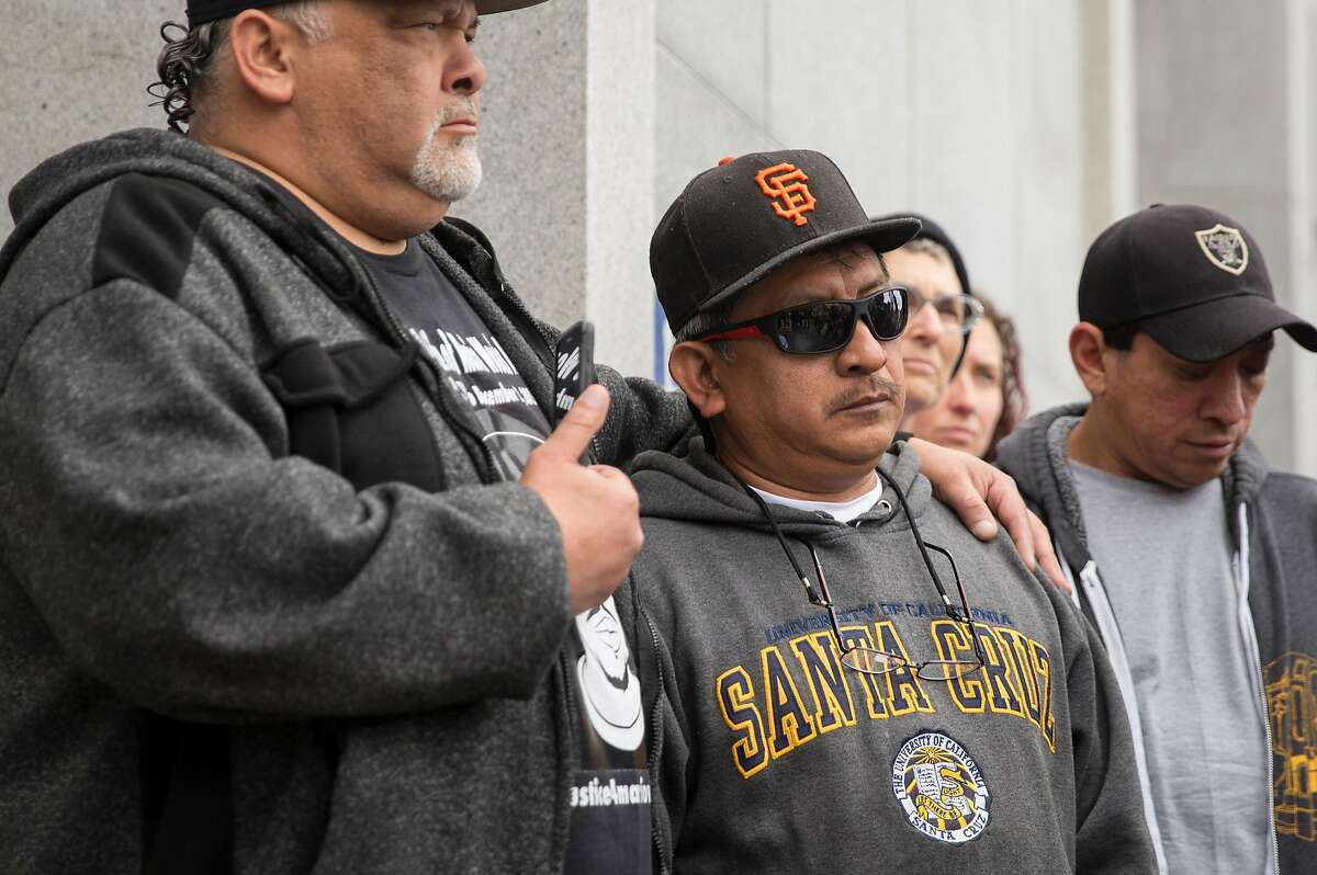 Luis Poot Pat, the cousin of Luis Gongora Pat who was shot and killed by police in 2016, and his cousin, becomes emotional as he stands on the steps of the Hall of Justice Thursday, May 24, 2018 in San Francisco, Calif. following the announcement of San Francisco District Attorney George Gascon's decision not to charges for the officers who shot and killed Luis Gongora Pat and Mario Woods.