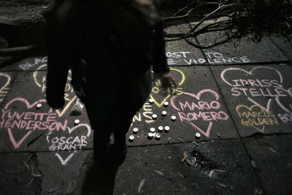 A member of the community stands near chalk art showing the names of those killed by police at the site where Mario Woods was shot and killed by San Francisco Police to commemorate the young man in the Bayview district of San Francisco, Calif., on Thursday, December 3, 2015.