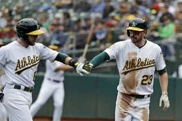 Oakland Athletics' Matt Joyce (23) shakes hands with teammate Jed Lowrie after Joyce scored on a sacrifice fly by Lowrie in the first inning of a baseball game agains the Seattle Mariners, Thursday, May 24, 2018, in Oakland, Calif. (AP Photo/Marcio Jose Sanchez)