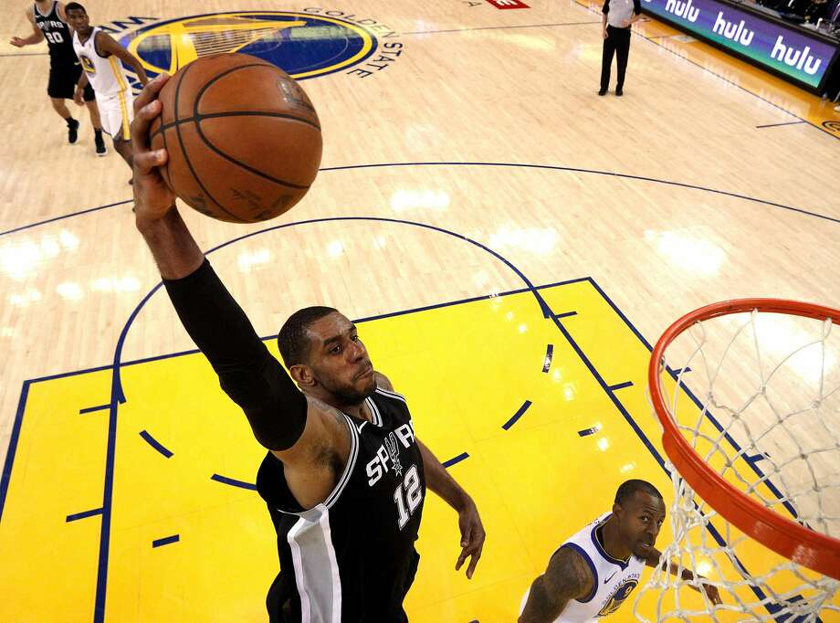LaMarcus Aldridge (12) dunks over Andre Iguodala (9) in the second half as the Golden State Warriors played the San Antonio Spurs in Game 5 of the first round of the Western Conference Finals at Oracle Arena in Oakland, Calif., on Tuesday, April 24, 2018. The Warriors won 99-91 to win the series and advance to the second round. Photo: Carlos Avila Gonzalez / The Chronicle