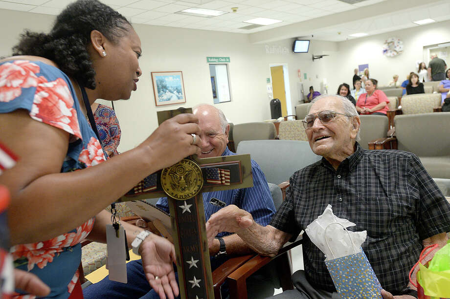 "WWII veteran and former Port Neches Mayor Thomas ""T.J."" Sasser and his son Ron Sasser (at left) react as his social worker Mary Wilson presents a gift while family, friends and caregivers with the Veterans Administration gather to celebrate his 100th birthday at the Beaumont VA Outpatient Clinic Thursday, May 24. Photo taken Thursday, May 24, 2018 Kim Brent/The Enterprise Photo: Kim Brent / BEN"