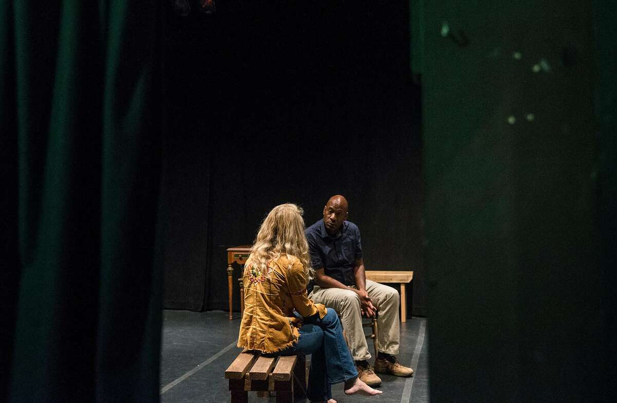 Actors Adrian Roberts, center, and Wendy Vanden Heuvel, left, read through lines for the production of Athol Fugard's