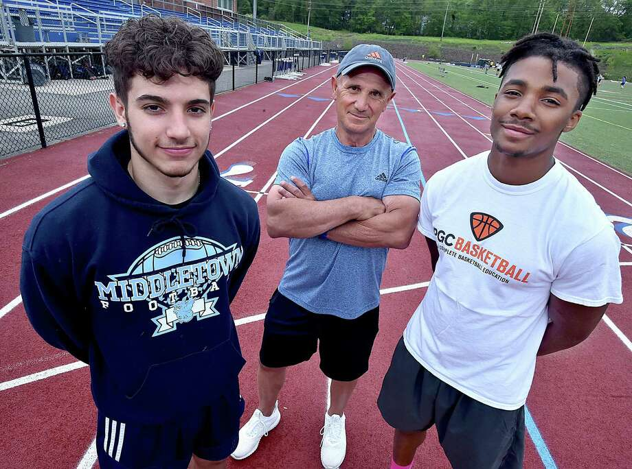 "Middletown sprinter Nico Cavaliere, left and jumper DeAaron Lawrence with sprinters/jumpers coach Alexander ""Sandy"" Tucci. Cavaliere qualified in the 100 meters and as part of the 4x100 team. Lawrence qualified in the high jump, long jump and triple jump. Photo: Catherine Avalone / Hearst Connecticut Media / New Haven Register"